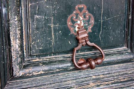 An old metal door handle knocker on a wooden door Stock Photo