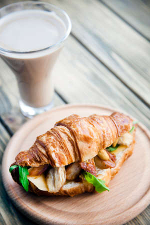 Roast chicken with greens sandwich croissant on a wooden tray and coffee with milk