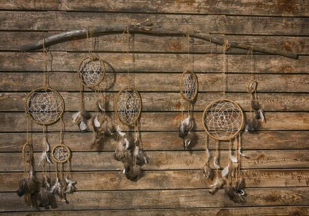Handmade dream catcher on background of wood wall. Tribal elements, feathers, beads. Spiritual decoration