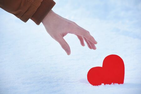 Lost red heart is alone on a valentines day, Heart on a cold winter snow, with a shining light around.Hand is picking up a red heart from the snow with care. Red heart stuck on a warm beautiful day.