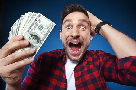 Hübscher bärtiger Mann im roten Hemd. Lustiger Kerl ist eine glückliche Gewinnerin, sie hält einen Haufen Geld, er ist glücklich und er kann es nicht glauben, er freut sich über einen Millionen-Dollar-Jackpot, jetzt ist er reich.