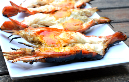 cleave: Three Grilled Giant River Prawn - shrimp it - cleave on - select focus - on white dish and wood background