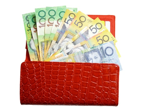 An open red-leather wallet filled with a fan of Australian banknotes on isolated white background photo