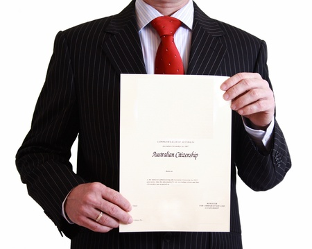 citizenship: Man in black suit holding Australian Citizenship certificate on isolated white background Stock Photo