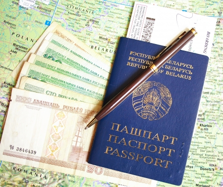 Belarusian passport and banknotes with pen and boarding pass over map background photo