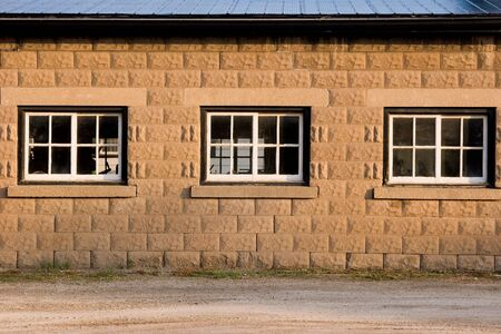 Tree windows on side of concrete block building during sunrise