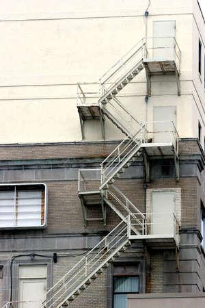 huir: Escalera de incendio en el costado del edificio de m�s edad Foto de archivo