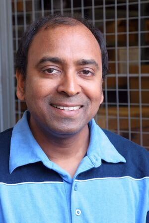 Middle aged south-Asian man with smile wearing a two tone blue shirt