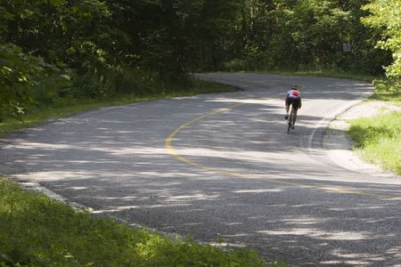 Cyclist negotiating a twisty  country roadway. Stock Photo