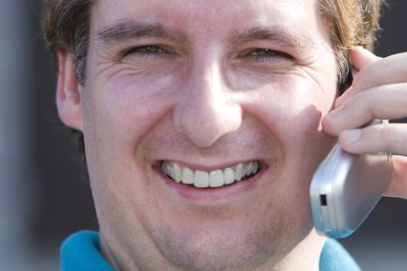 late thirties: Man in late thirties with blue shirt talking on a cell phone