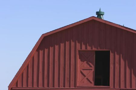Second floor door of a red barn against a blue sky