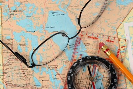 Glasses, map and compass Stock Photo