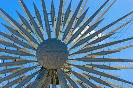Hub and spokes of a ferris wheel against a bright blue sky Stock Photo