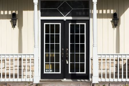 Double French doors with porch, pale yellow siding and white trim photo