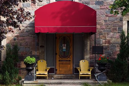 Doorway with large red awning, yellow chairs on patio and multi-colored brick