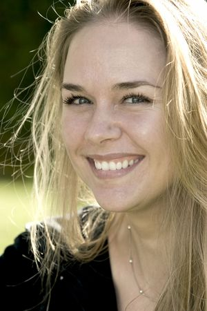 Beautiful blonde woman with green eyes and smiling. Taken with backlighting.