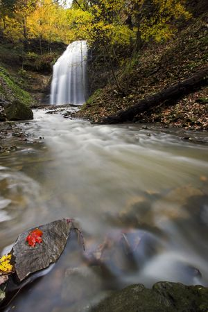 Wide angle image of a creek with waterfall in the background and red maple leaf on rock in the foreground. Stock Photo