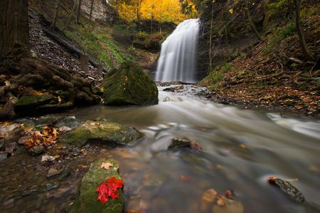Wide angle image of creek in a canyon with waterfall in the background and red maple leaf on a rock in the foreground. photo