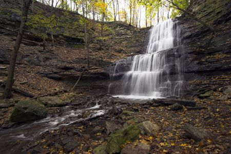 Waterfall with 3 levels falling into a canyon. Taken with a very wide angle lens with long exposure time. photo