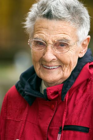 Smiling senior woman in red jacket with short hair wearing glasses against a blurry background. Narrow DOF with focus on the eyes.
