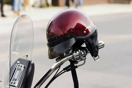Red helmut propped on the handlebars of a parked motorcycle Stock Photo - 681323