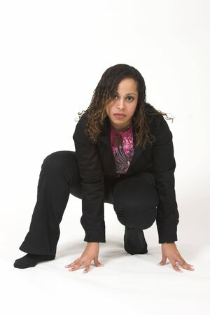 Pretty woman in a pounce position wearing a black suit. Stock Photo