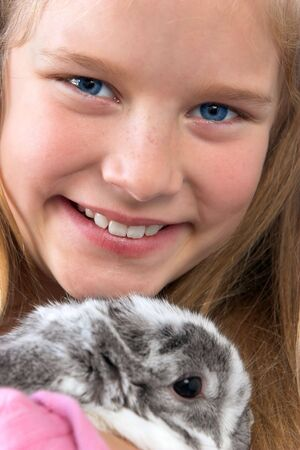 Young blond girl with pet gray and white rabbit.