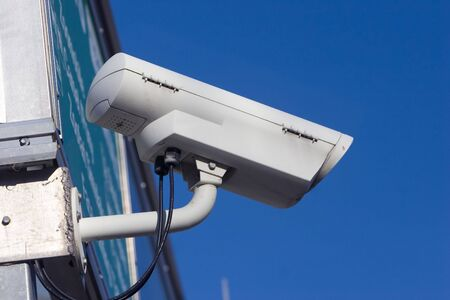 White surveillance camera mounted on the outside of a building Stock Photo