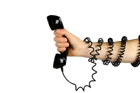Hand gripping telelphone with cord wrapped around his arm. Stock Photo