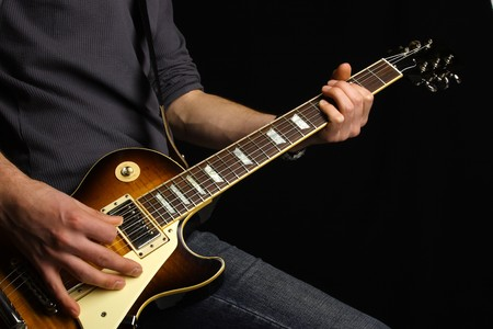 Close up of an electric guitar being played.