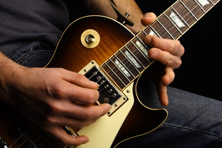 Close up of an electric guitar being played. photo