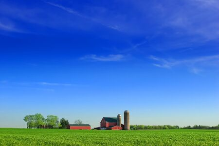 Red barn and silos on a farmstead with expansive blue sky. Stock Photo