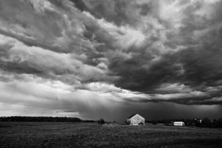 Landscape image of a summer storm over a farm field in B&W.