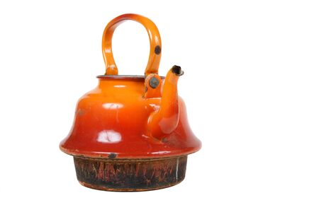 Old orange kettle with rusty bottom against a white background