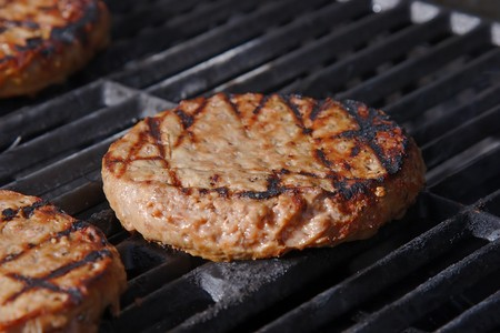 Juicy burger grilling on a hot barbeque. Stock Photo