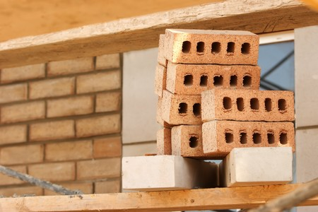 Stack of bricks on a scaffold at a construction site.