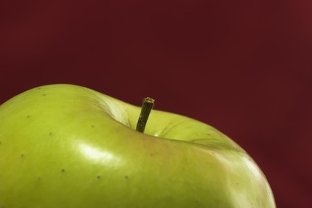 Stem of a green apple against a red background. Focus is on stem with narrow depth of field.