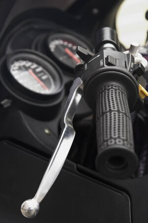 Close up of a motorcycle handle bar with gauges in the background. Focus in on the choke.