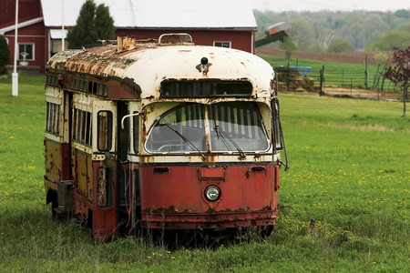 Old red and yellow, rusted and abandoned trolley car in a farmers field.