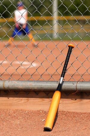 Yellow and black baseball bat leaning again a fence with player in the background. Stock Photo