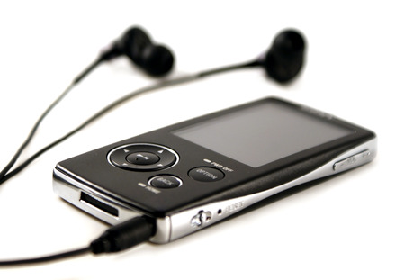 A black mp4 player with a par of modern headphones