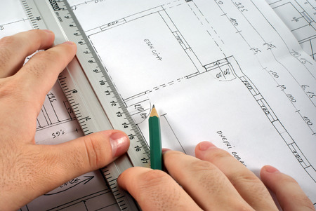 Hand with ruler and pencil writing on blueprint