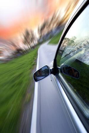 Gray car speeds through a country lane photo