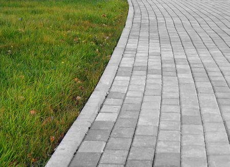 Detail of a concrete sidewalk with grass on one side photo