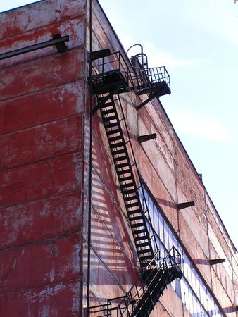 building external: External metallic staircase on the wall of the industrial building