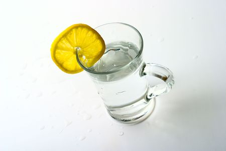 Transparent glass of water with a lemon on a white background photo