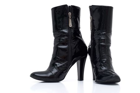 Womens patent leather boots with a heel. Isolated on a white background. Natural shade. Studio work. photo