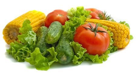 Vegetables on white background: tomatoes, cucumbers, corn on the leaves of lettuce. Stock Photo - 4715756