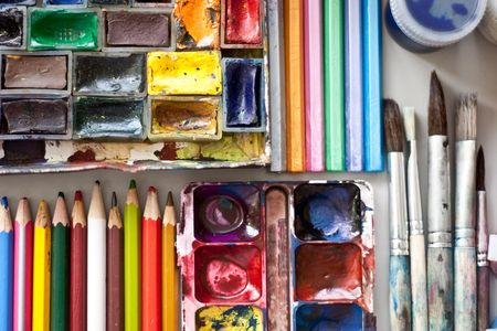 Items for drawing and art: watercolor paint, brushes, colored pencils. Stock Photo