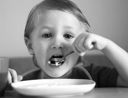b w: A little boy eats. B & W photo.